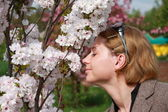 Woman smelling spring flowers outdoors — Stock Photo