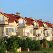 Stock Photo: Row of similar houses over blue sky