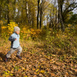 Boy running in autumn scenery - Stock Photo