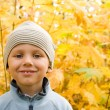 Happy boy smiling in autumnal scenery — Stock Photo