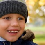Boy smiling in autumn scenery — Stock Photo