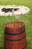 Red barrel with metal skewers — Stock Photo