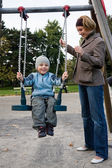 Mother and son on swing — Stock Photo