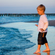 Boy going to sea water in sunset light — Stock Photo #2362075