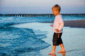 Boy going to sea water in sunset light — Stock Photo