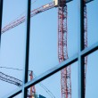Construction cranes reflection — Stock Photo