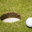 Golf ball close to a hole — Stock Photo