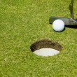 Stock Photo: Putting golf ball to a hole