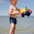 Boy with toy car on beach — Stock Photo