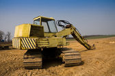 Dirty yellow excavator — Stock Photo