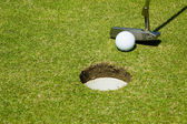 Putting golf ball to a hole — Stock Photo