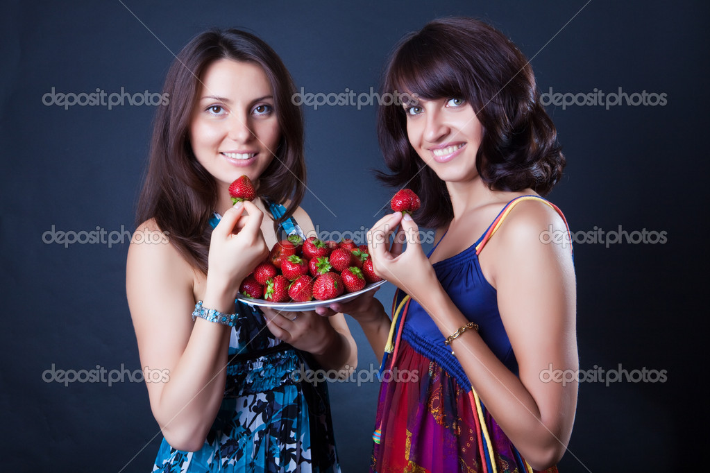 Two beautiful girls eat a strawberry — Stock Photo #1718221