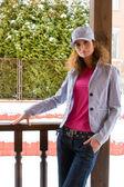 Beautiful young woman stand on a verandah — Stock Photo
