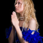 Beautiful girl in a dark blue dress prays — Stock Photo #1757198