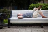 мужчина лежит на скамейке в парке — Стоковое фото