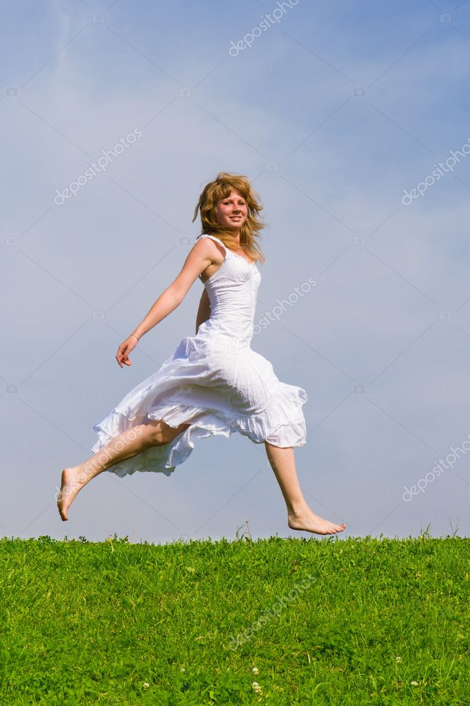 Girl runs on a grass on a background of the blue sky — Stock Photo #1756614