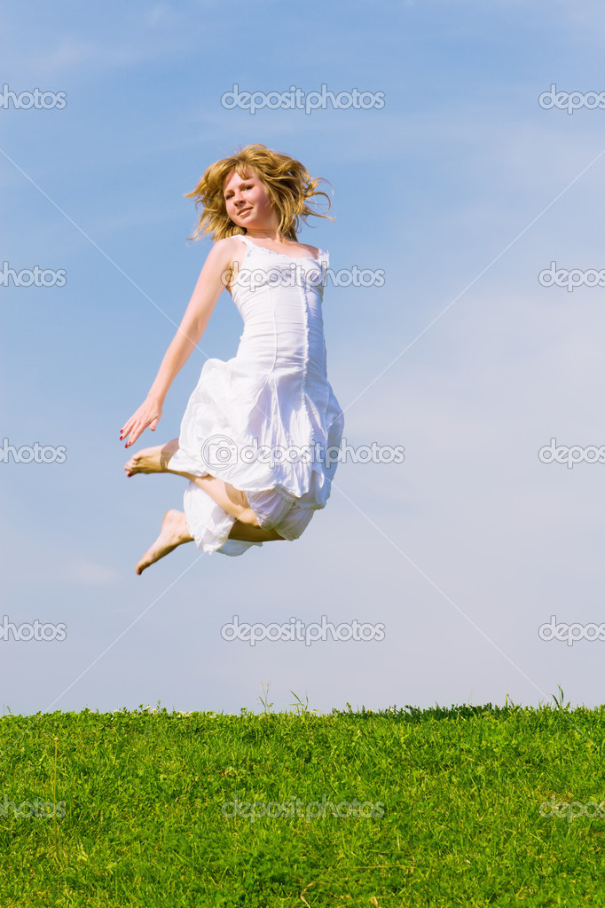 Girl jumps on a green grass on a background of the blue sky — Stock Photo #1756624