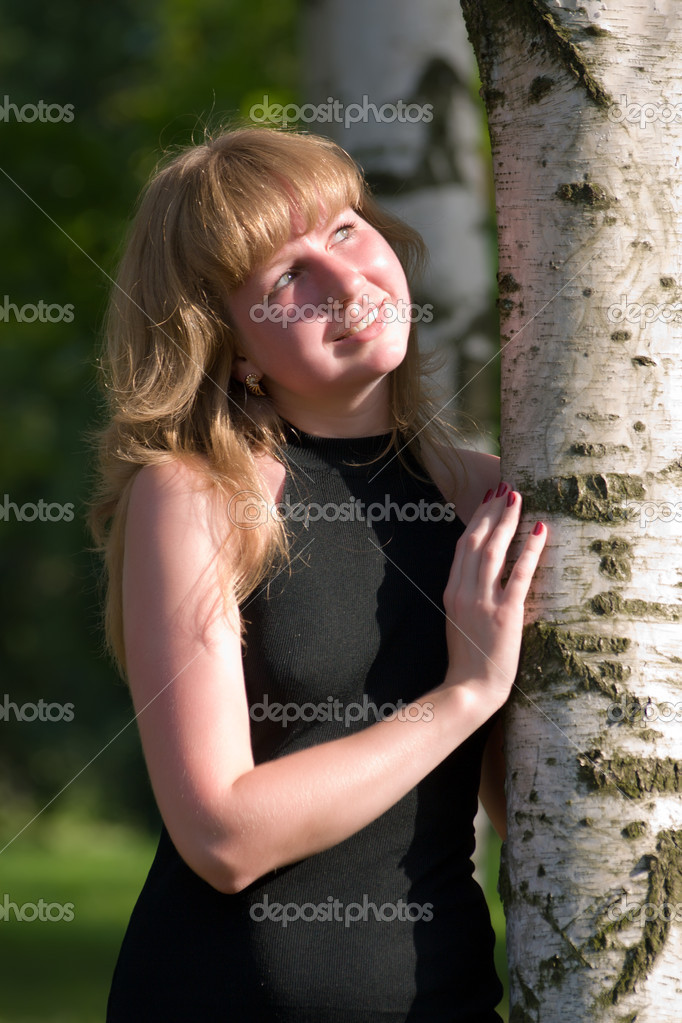 Beautiful girl in a black dress near to a tree — Stock Photo #1756639