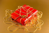 Red gift on gold background — Stock Photo