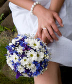 Hands of a bride with a ring and bouquet — Stock Photo