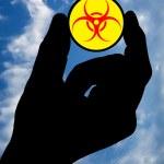 Hand with biohazard symbol and sky — Stock Photo