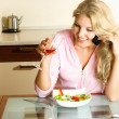Girl eating and taking on the cellphone — Stockfoto