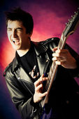Excited young man playing guitar — Stock Photo