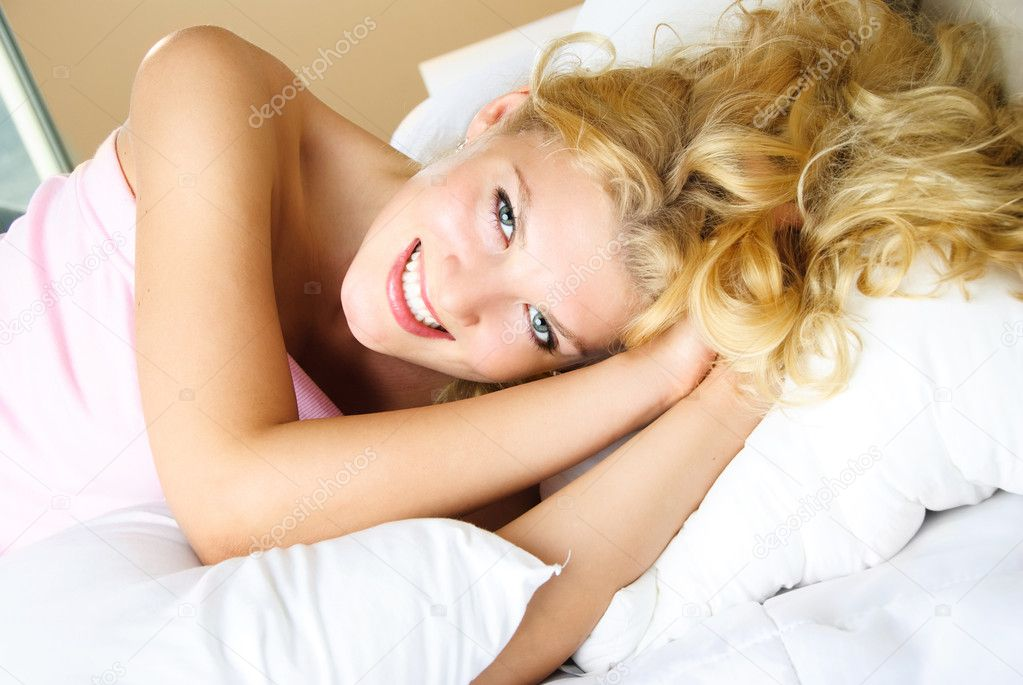 Beautiful young woman with long blond hair at home in her bed — Stock Photo #1798058