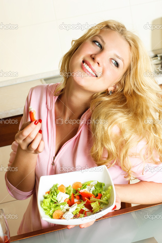 Pretty young woman at home in the kitchen eating salad  — Foto Stock #1798654