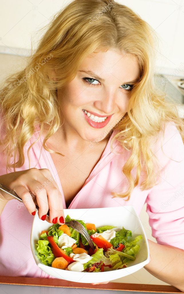 Pretty young woman at home in the kitchen eating salad of vegetables  Stock Photo #1798669