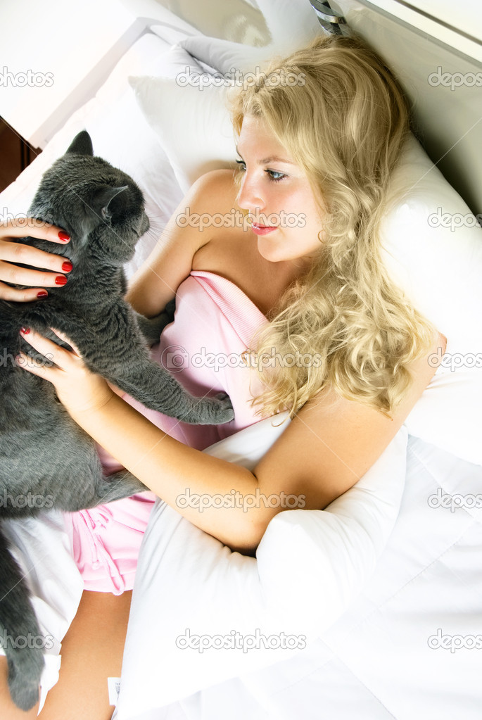 Beautiful young blond woman in bed at home with her cat — Stok fotoğraf #1799714