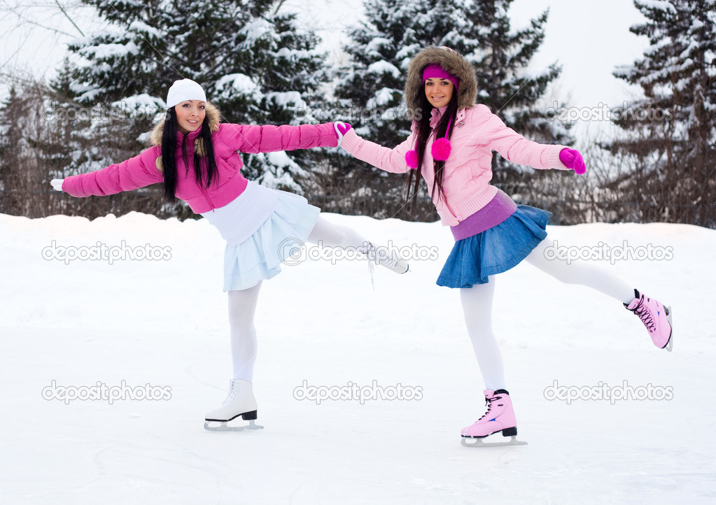 Two beautiful girls wearing warm winter clothes ice skating — Photo #1809467