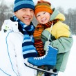 Father and son go ice skating - Stock Photo