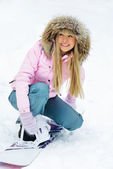Woman putting on a snowboard — Stok fotoğraf