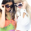 Girls trying on sun glasses - Stock Photo