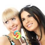 två glada tjejer med en godis — Stockfoto
