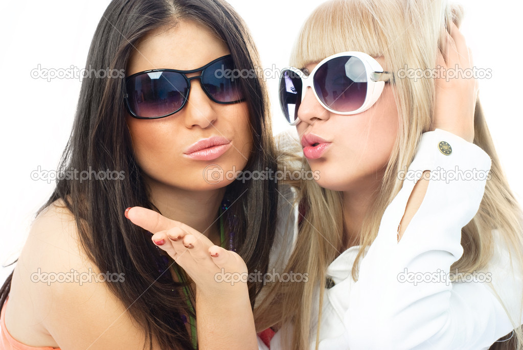 Two young glamorous friends wearing sun glasses and sending us an air kiss — Stock Photo #1826663