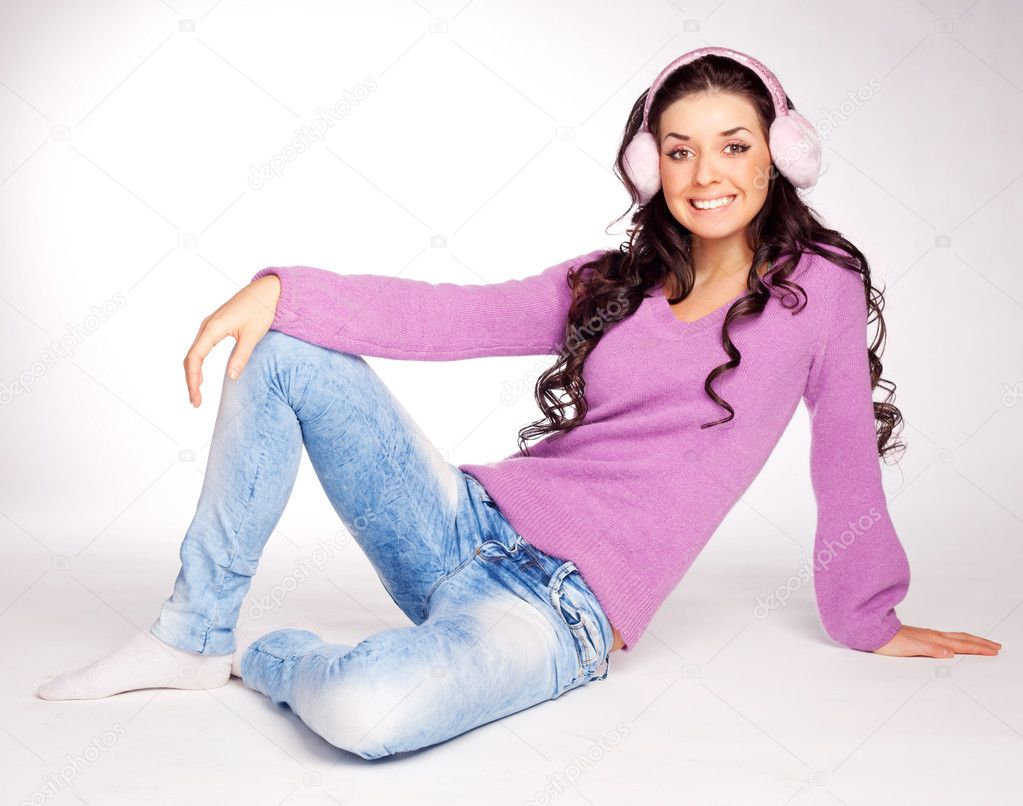 Dreamy young brunette woman wearing pink earmuff — Stock Photo #1847536