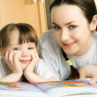 Stock Photo: Mother and daughter reading a book