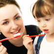 Mother and daughter brushing teeth — Stock Photo