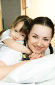Mother and daughter on the bed — Stock Photo