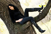 Melancholic girl sitting on the tree — Stock Photo
