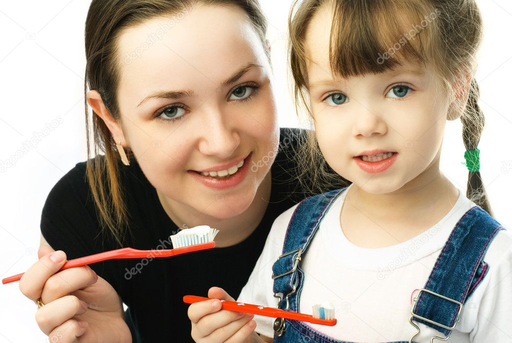 Young beautiful mother teaching her little daughter brushing teeth  Stock Photo #1871499