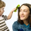 Girl brushing her mothers hair — Stock Photo