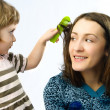 Girl brushing her mothers hair - Stok fotoğraf