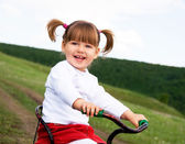 Cute two-year old girl riding a bysicle — Stock Photo