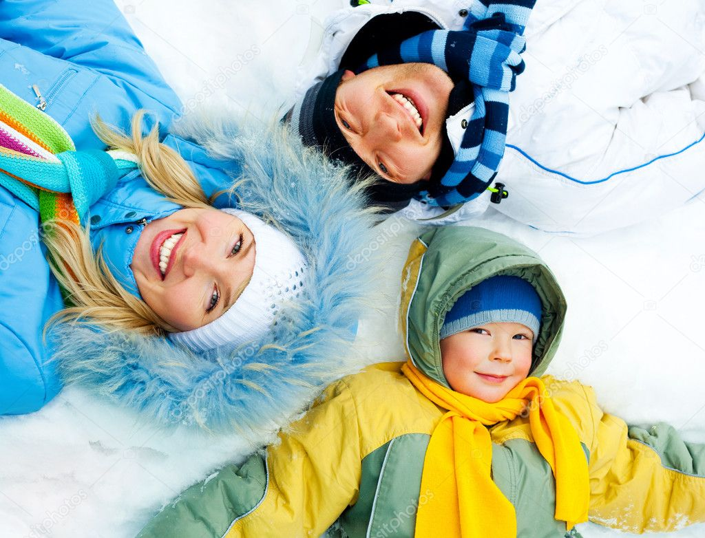 Young parents and their son wearing warm winter clothes lie on the snow  Stock Photo #1891195