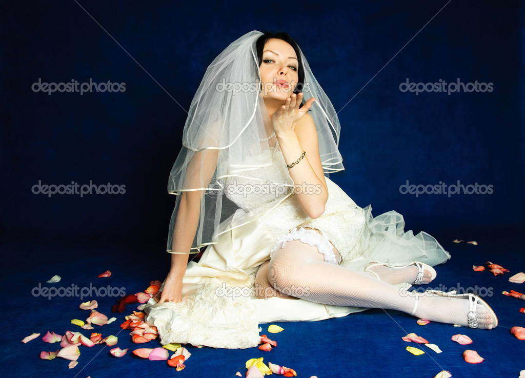 Studio portrait of a beautiful bride sitting on the floor covered with rose leaves and sending us an air kiss — Stock Photo #1893935