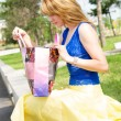 Pretty girl looking into her shopping bag — Stock Photo