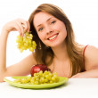Beautiful woman with an apple and grapes — Stock Photo